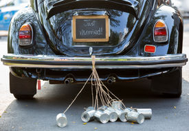 stock photo of marriage ceremony  - Just married sign and cans attached vintag car - JPG