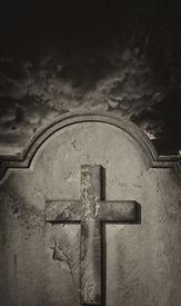 stock photo of headstones  - Spooky old weathered cemetery headstone against stormy atmospheric sky - JPG