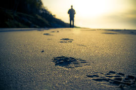 foto of footprint  - Footprint in the sand and the figure of a man cultivating Nordic walking - JPG