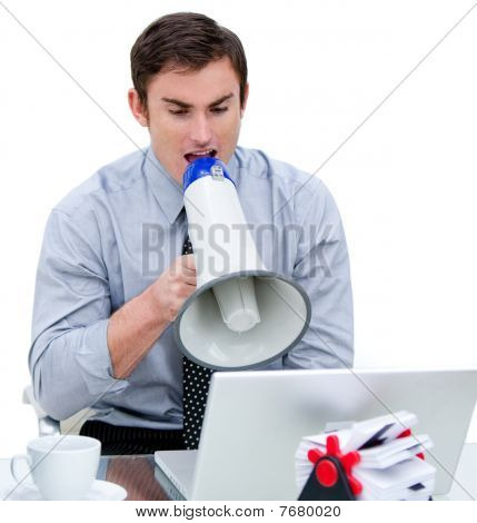 Angry Businessman Yelling Through A Megaphone Sitting At His Desk