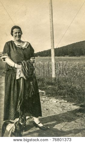 GERMANY, CIRCA 1930:  Vintage photo of  overweight woman walking with a little dog