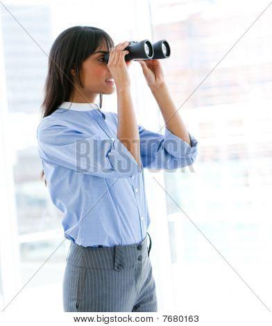 Confident Female Executive Looking Through Binoculars
