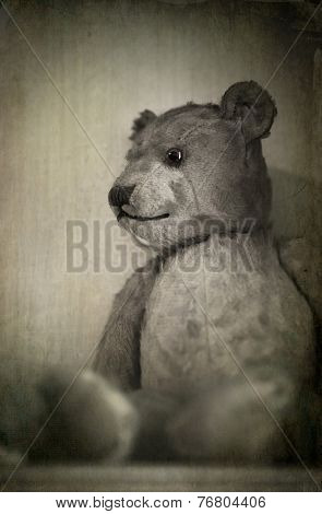 Nostalgic image of an old, well loved bear. Sepia effect with texture.