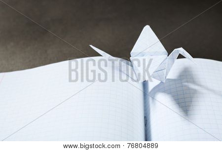 Origami cranes on notebook on grey background
