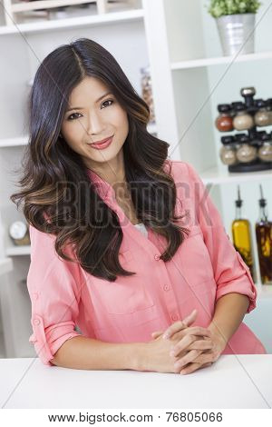 Beautiful young Asian Chinese woman or girl at home in her kitchen smiling