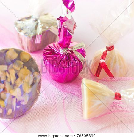 Assorted white chocolate in shiny wrapper on a colorful background