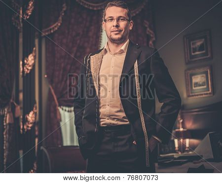 Middle-aged man trying on custom made suit in luxury vintage interior