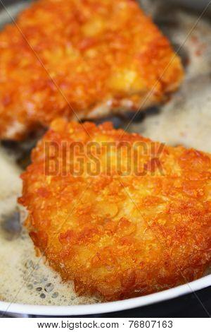Crispy chicken fillet in the frying pan, closeup