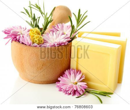 Bars of natural soap and wooden mortar with fresh herbs and flowers isolated on white