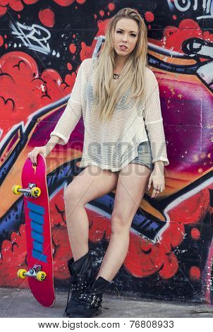 Beautiful and sexy street girl with her skateboard