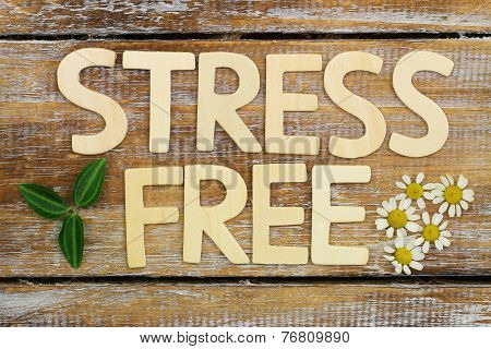 Stress free written with wooden letters on rustic wooden surface with fresh chamomile flowers