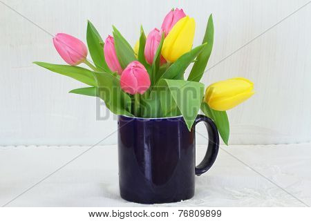 Pink and yellow tulips in navy blue mug