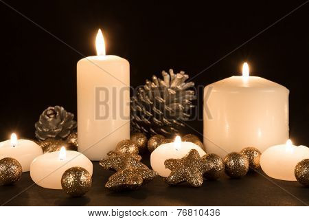 Burning Candles With Pine Apples And Gilded Stars On A Black Background