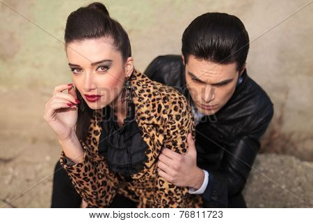 Beautiful fashion woman looking at the camera while her lover is looking away and holding her arm.