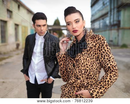 Beautiful fashion woman playing with her earring, holding one hand in pocket while her lover is standing behind her looking away with his hands in pocket.