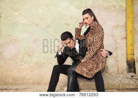 Handsome young man sitting and thinking, holding his girlfriend on his lap.
