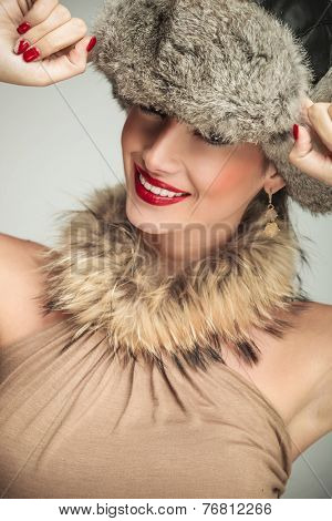 portrait of a beauty woman wearing a fur hat and smile to the camera, hand on cap