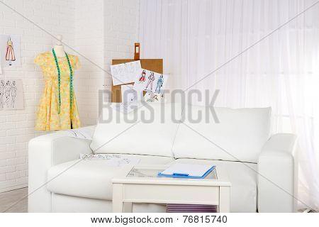 Fashion designer studio with professional equipment, sketches, mannequin, cloth