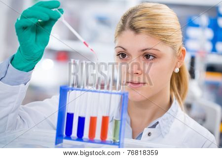 young women science professional pipetting solution into the glass test tube.