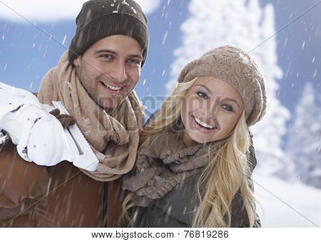 Happy couple smiling in snowfall, man holding ice skates.