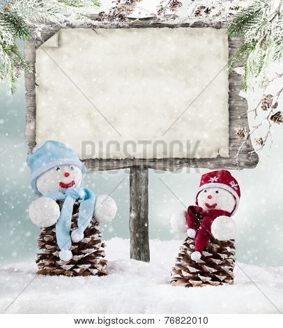 Winter holiday happy snow men with blur landscape on background. Empty wooden board for copyspace