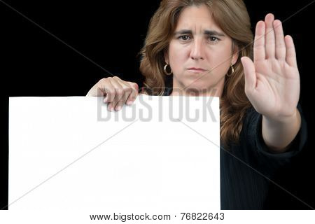 Serious woman gesturing to stop and holding a white banner with space for text isolated on a black background