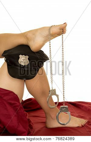 Woman Legs And Red Sheet Plice Hat Handcuffs On Foot Close