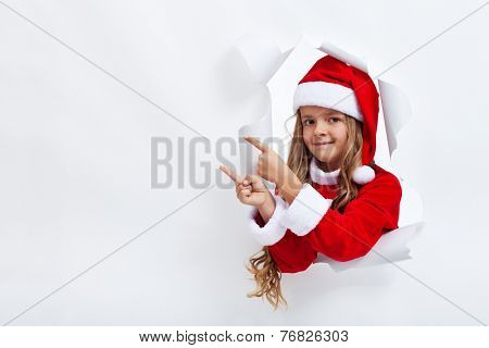 Girl in santa claus costume pointing to copy space - through an opening in billboard
