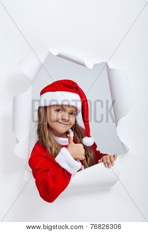 Christmas outfit girl giving thumbs up sign - leaning out of a jagged edge hole in paper layer
