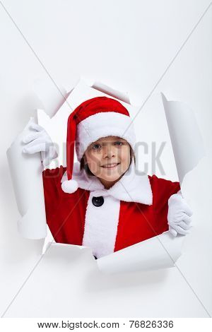 Opening the holidays season - boy looking through jagged edge hole in white paper layer