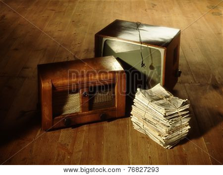 Pile Of Old Newspapers, Radio And Television On Wooden Floor