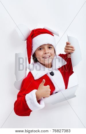 Happy boy opening christmas season - widening a hole in white paper layer