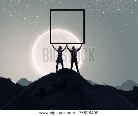 Silhouettes of young couple holding banner above head