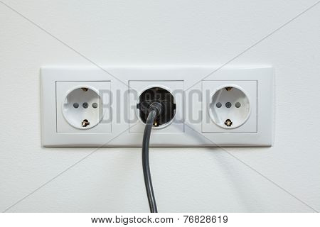 Close up photo of a black power plug plugged in a triple electric socket