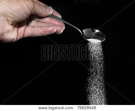 Sugar being poured from spoon with a dark background