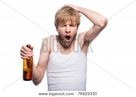 Young man with hangover holding beer bottle