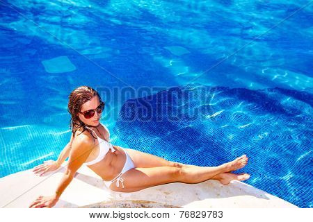 Beautiful girl relaxing near swimming pool at luxury resort.