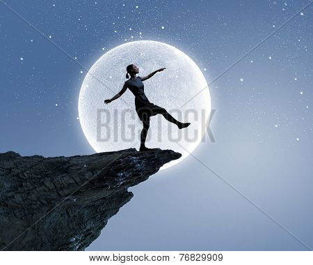 Young woman walking at mountain edge at night