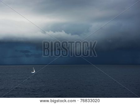 Lonely sailing boat menaced by stomy ocean clouds