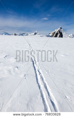 Ski track on fresh snow. Winter sport background with the famous Matterhorn peak - Zermatt ski resort, Switzerland, Europe.