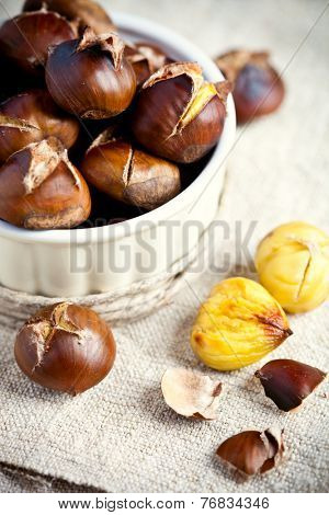 roasted chestnuts in bowl on wooden background