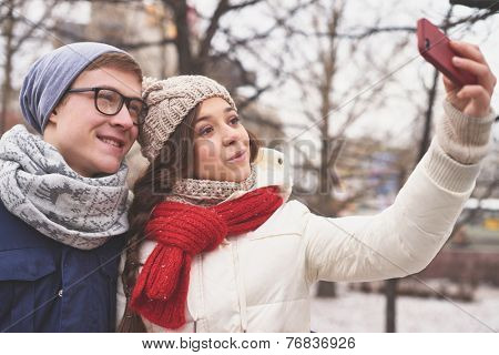 Affectionate young dates in casual winterwear taking photo of themselves outdoors