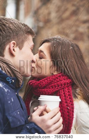 Portrait of amorous young couple kissing outdoors