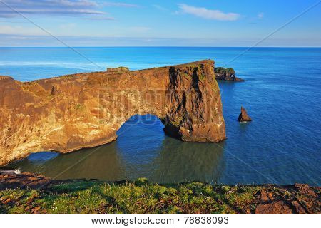 The cape Dirkholaey in the south of Iceland. A sunset in July. The enormous rock- elephant it is lit with a summer