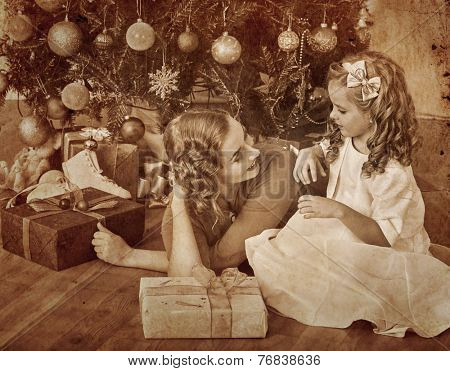 Child with mother receiving near Christmas tree.