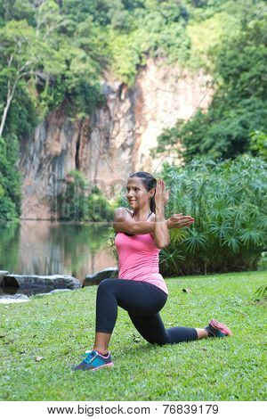 Sporty woman stretching tricep back of arm while doing lunge in an outdoor park.