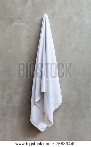White Towel Is Hanging On The Exposed Concrete Wall In The Bathroom