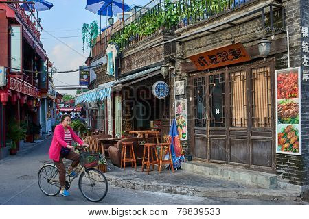 Beijing , China - September 24, 2014:  Chinese woman cycling in traditional Hutong streets Beijing China