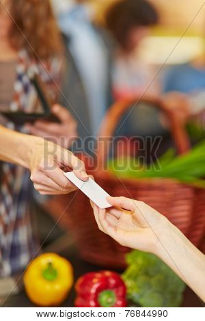 Hand of customer giving credit card to supermarket teller at checkout