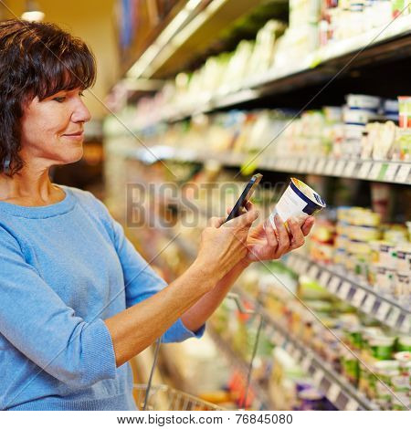Elderly woman with smartphone scanning barcode of yogurt in a supermarket